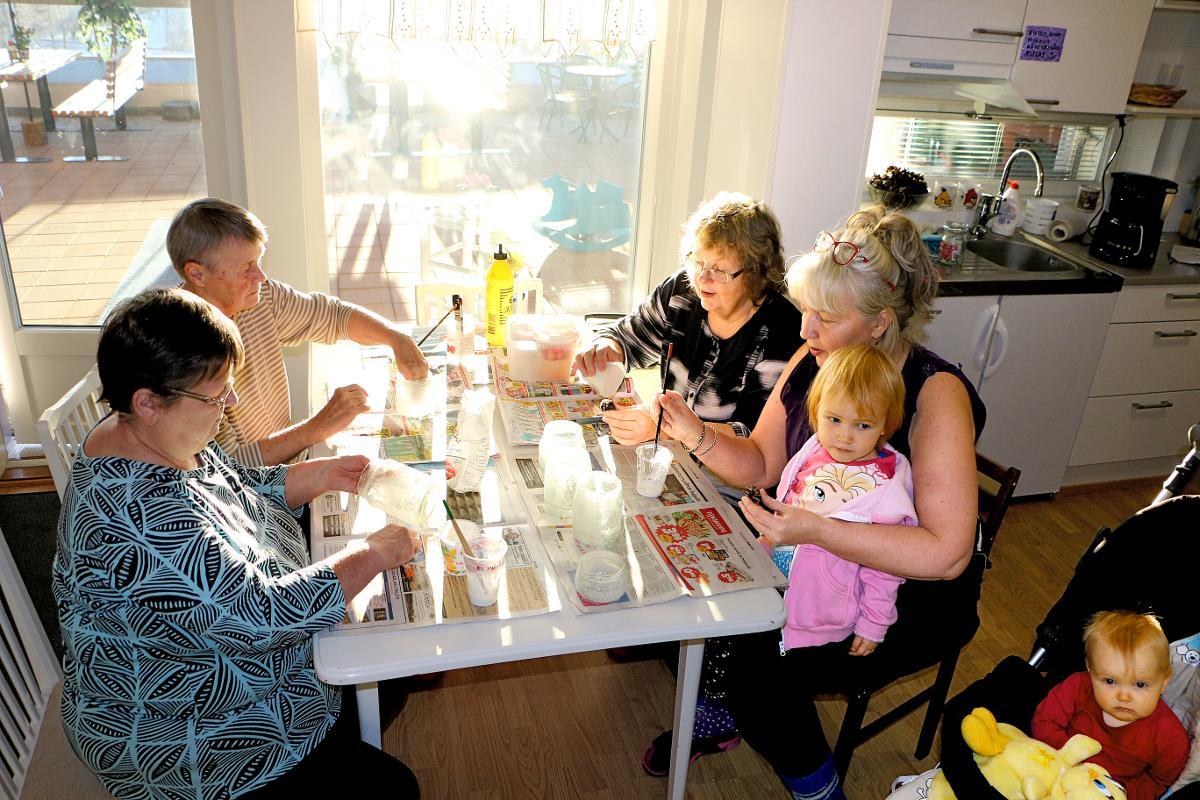 Kuva: Senioritalossa on kokoonnuttu syksyn aika usein yhteen askartelemaan lasipurkeista lyhtyjä itsenäisyyspäivää varten. Lyhtyjä viimeistelevät Salli Rossi, Ritva Taskila, Merja Korkeakoski sekä Ritu-Tuuli Alatalo lapsenlapsiensa Mintun ja Meten kanssa.
