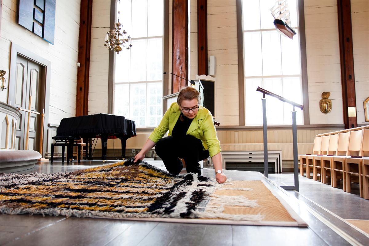 Kuva: Pastori Iida Glumoff asettelee vihkiryijyä kirkon alttarille. Yleensä tämän työn tekee suntio.