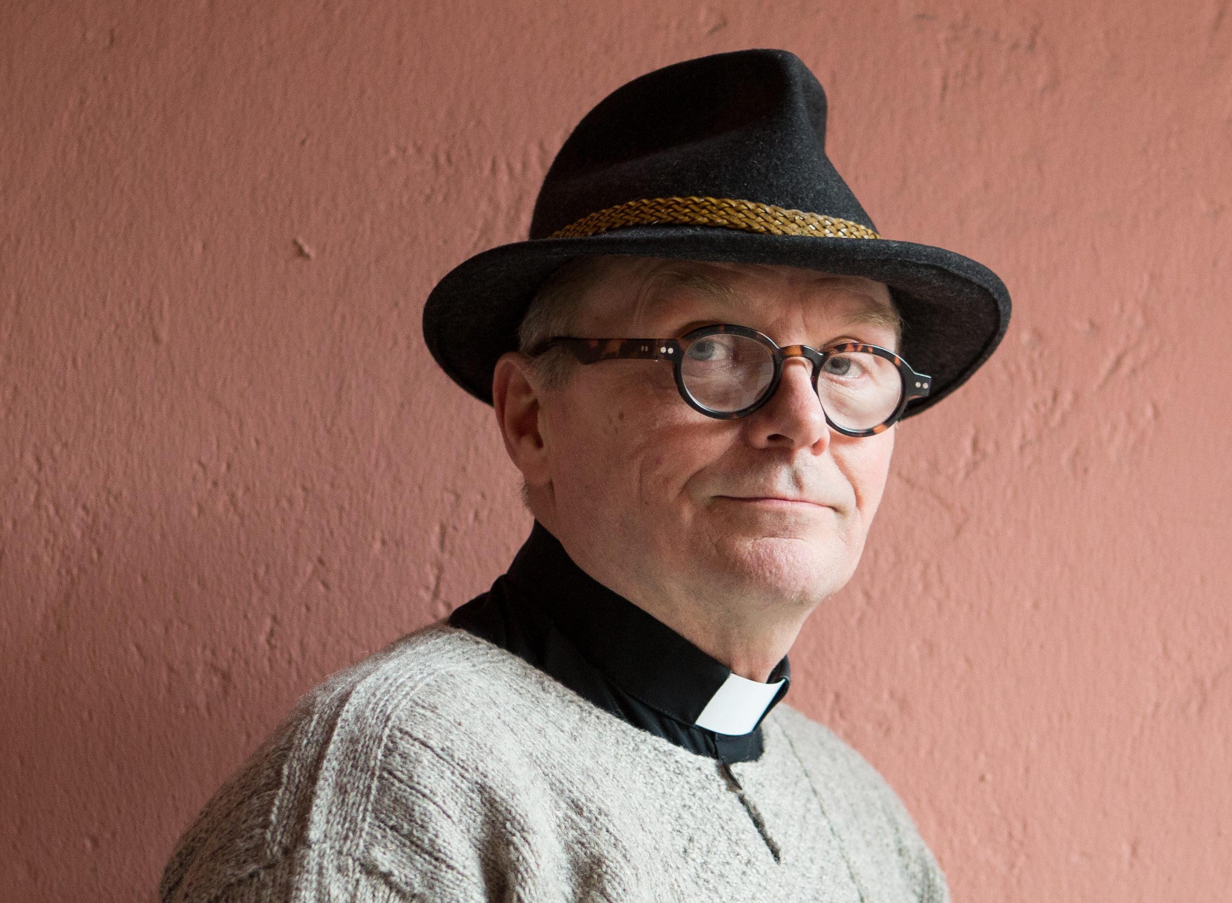 Punertavan seinän edessä mies luotolaispaidassa ja papinkauluksessa, hattu päässään.