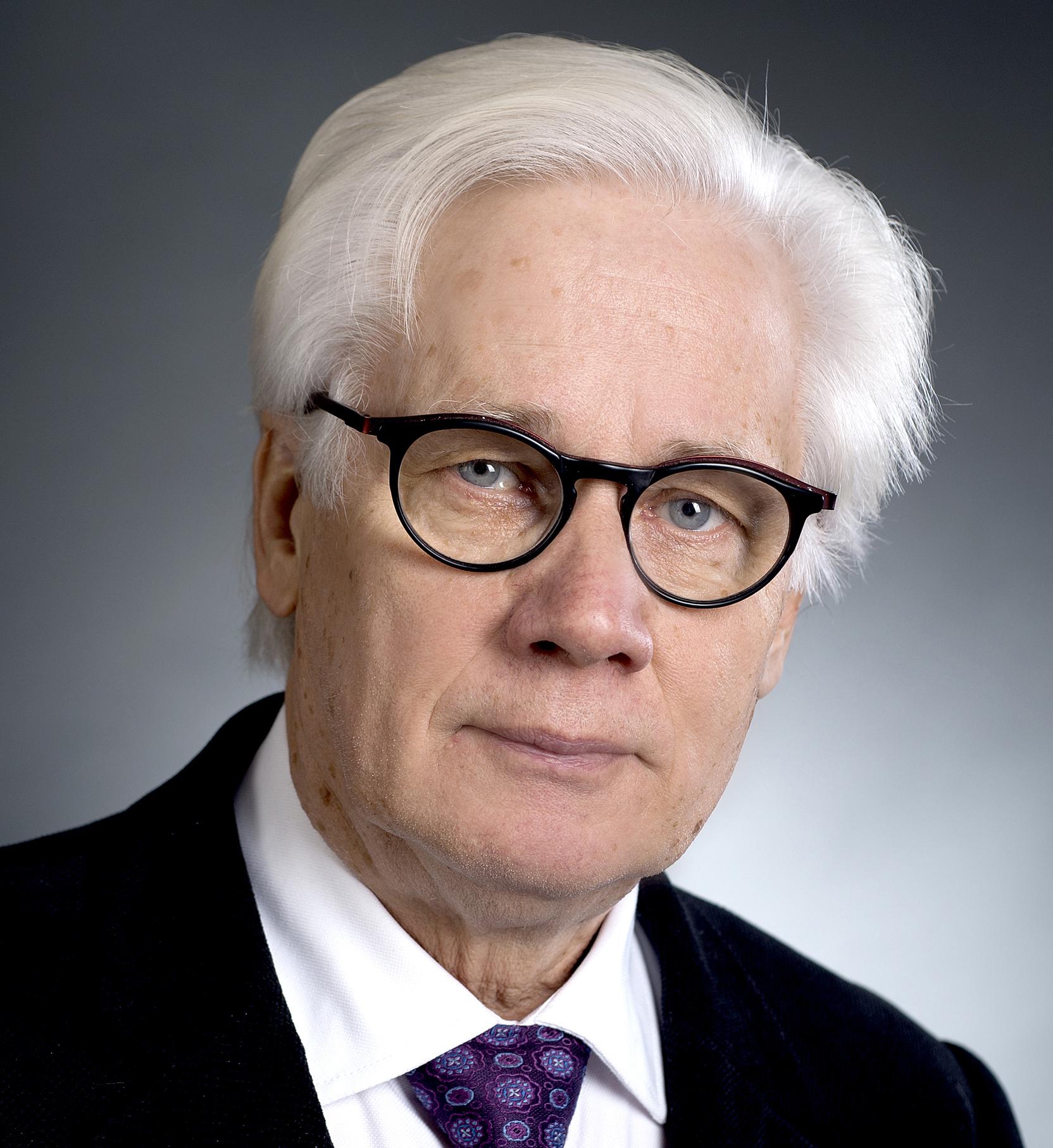 Valkeatukkaisen ja silmälasipäsen miehen kuva.