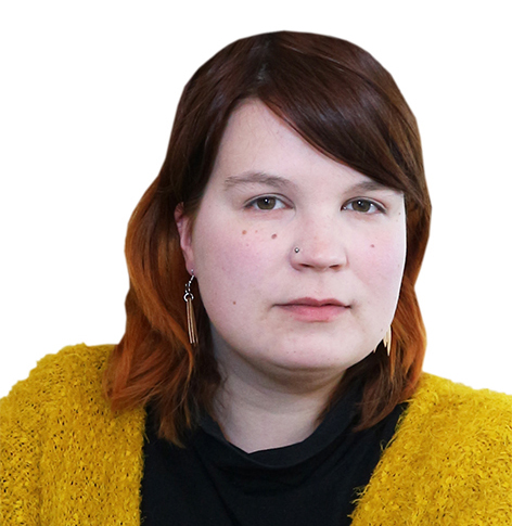 Punaruskeahiuksinen nainen mustassa paidassa ja keltaisessa neuletakissa katsoo kameraan.