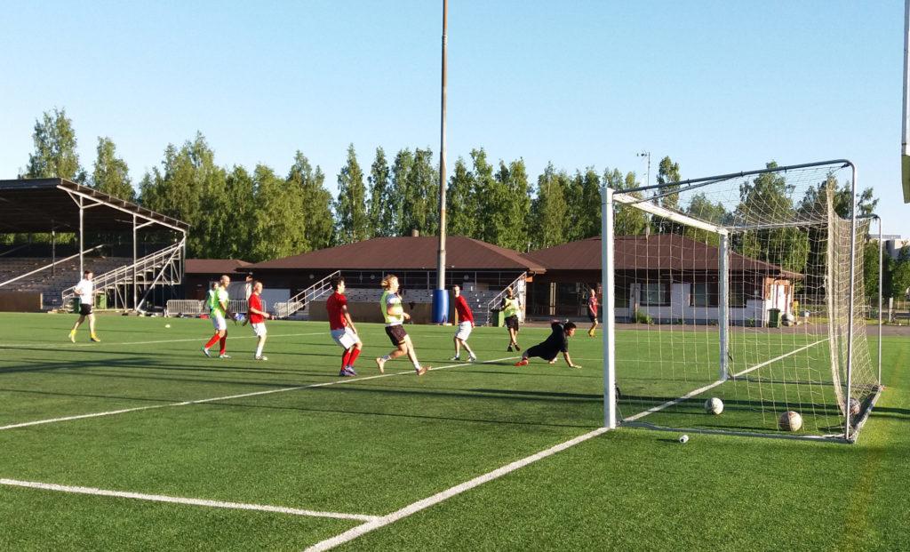 Jalkapallojoukkue harjoittelee, yksi pelaajista potkaisee pallon maaliin maalivahdin ohi