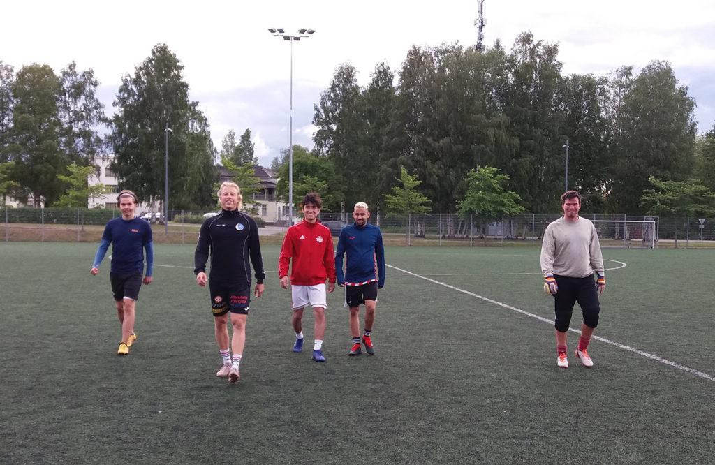 Viisi miestä kävelee kohti kameraa jalkapallokentällä