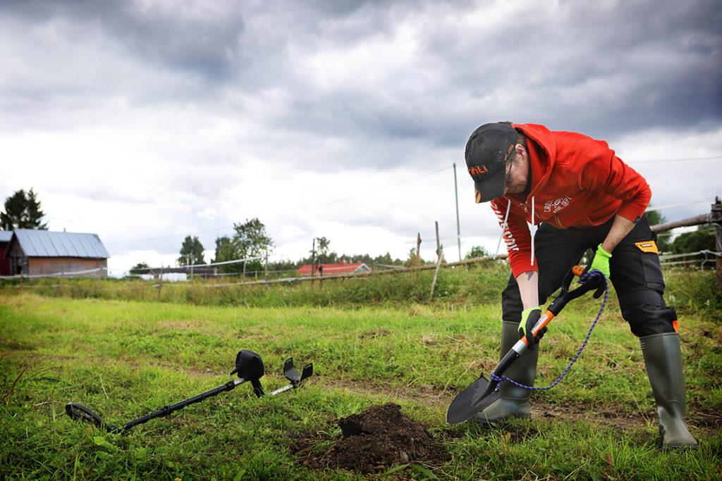 Mies kaivaa lapiolla kuoppaa peltoon etsiessään metallia.