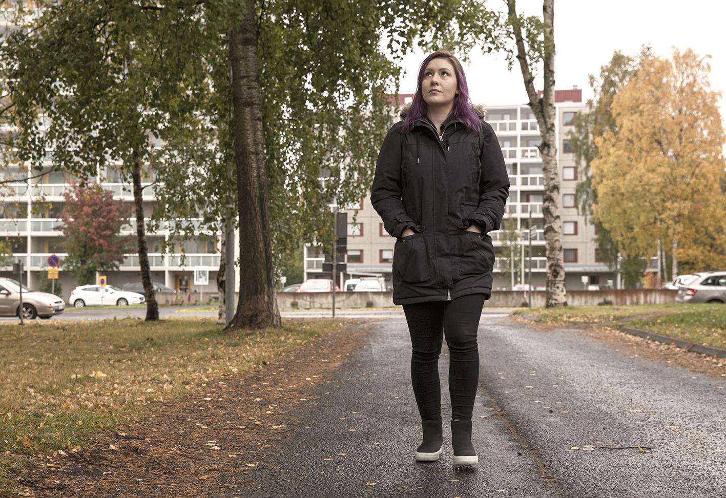 Nuori nainen kävelee syksyisessä kaupunkimaisemassa.