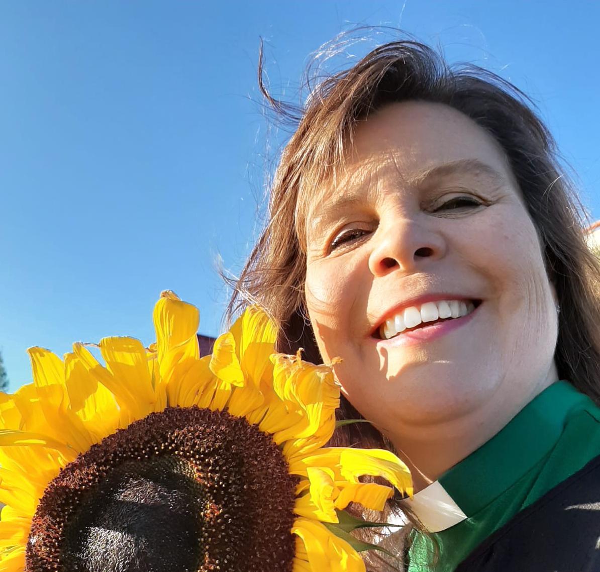 Nainen hymyilee auringonkukka vierellään.
