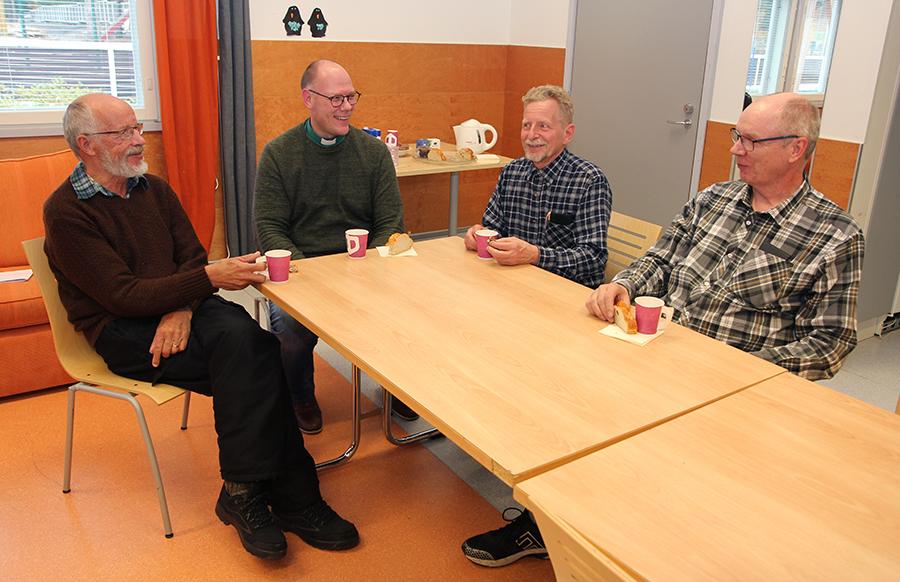 Neljä miestä istuu pöydän ääressä kahvikupit edessään.