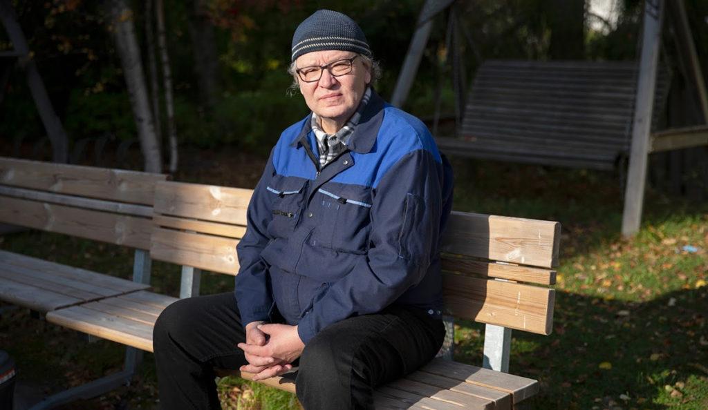 Risto Askeli istuu ulkona penkillä auringonpaisteessa.