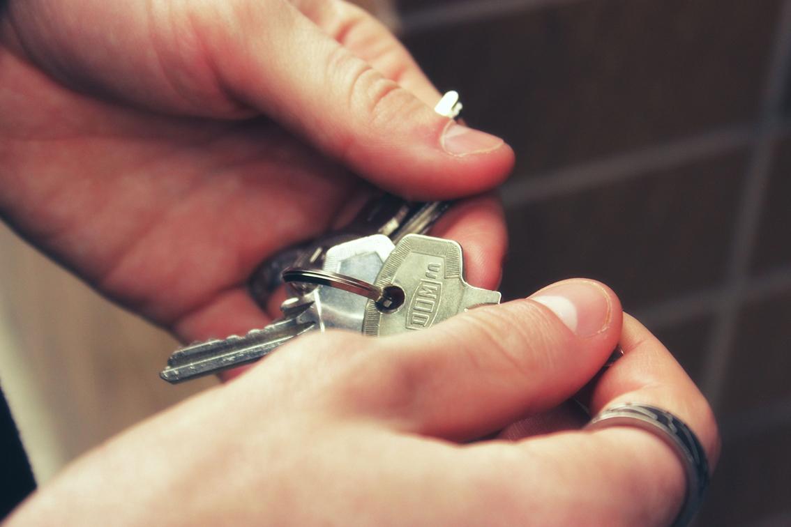 Kädet, jotka pitelevät avainnippua.