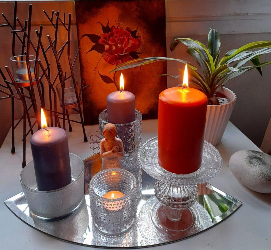 Kynttilöitä ja enkelipatsas.