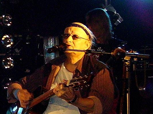 Huivipäinen mies soittaa kitaraa ja laulaa mikrofoniin.
