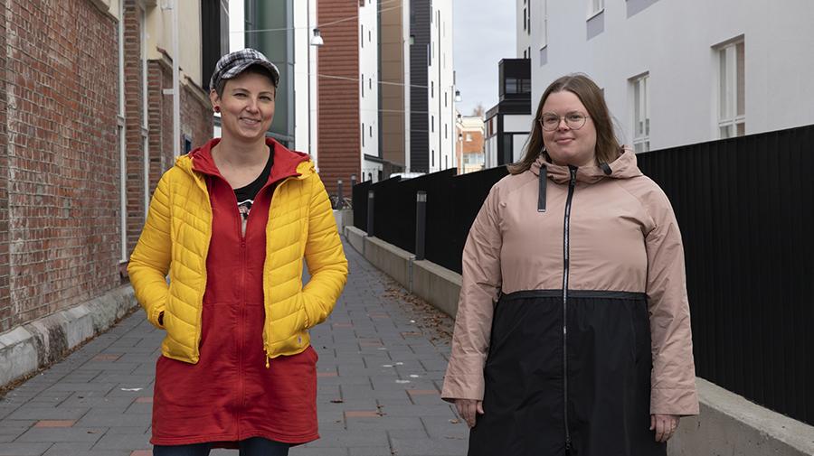 Kaksi naista seisoo rinnakkain kerrostalojen kupeessa.