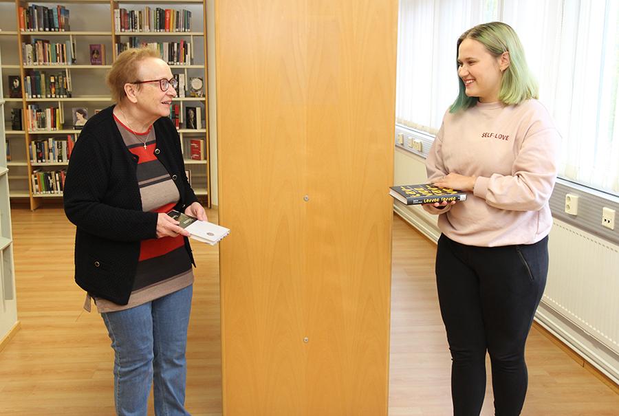 Kaksi naista katsoo toisiaan kirjat kädessä ja hymyilee.