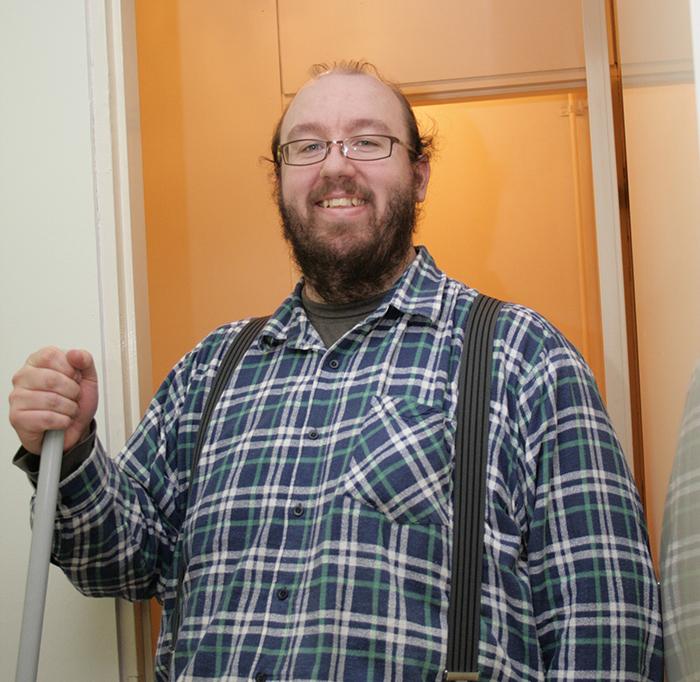 Henkselihousuihin ja ruutupaitaan pukeutunut mies pitää kädessään harjanvartta ja hymyilee.