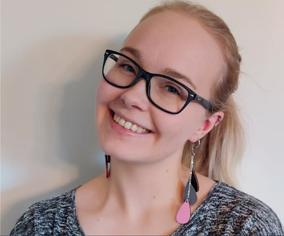 Vaaleahiuksinen nuori nainen hymyilee isot korvakorut korvissaan.