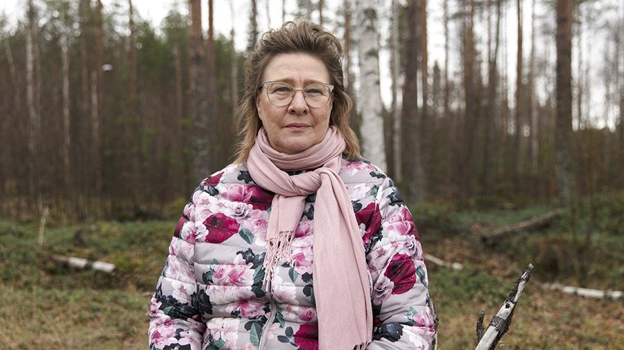 Nainen istuu metsässä ja katsoo kameraan.