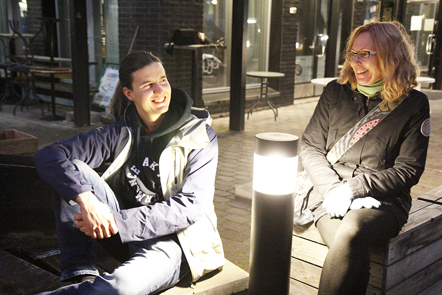 Okko Tuuri ja Kirsi Junnonaho istuvat pihavalon luona ja hymyilevät.