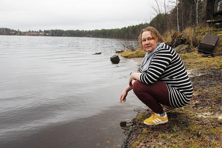 Nainen on joen äärellä ja katsoo kameraan.