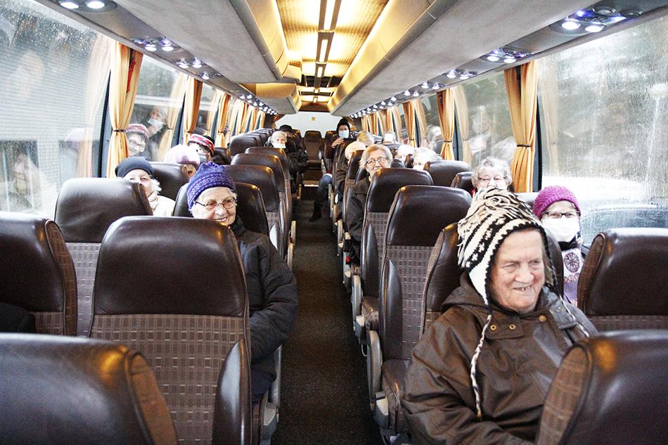 Naisia istuu bussin penkeillä.