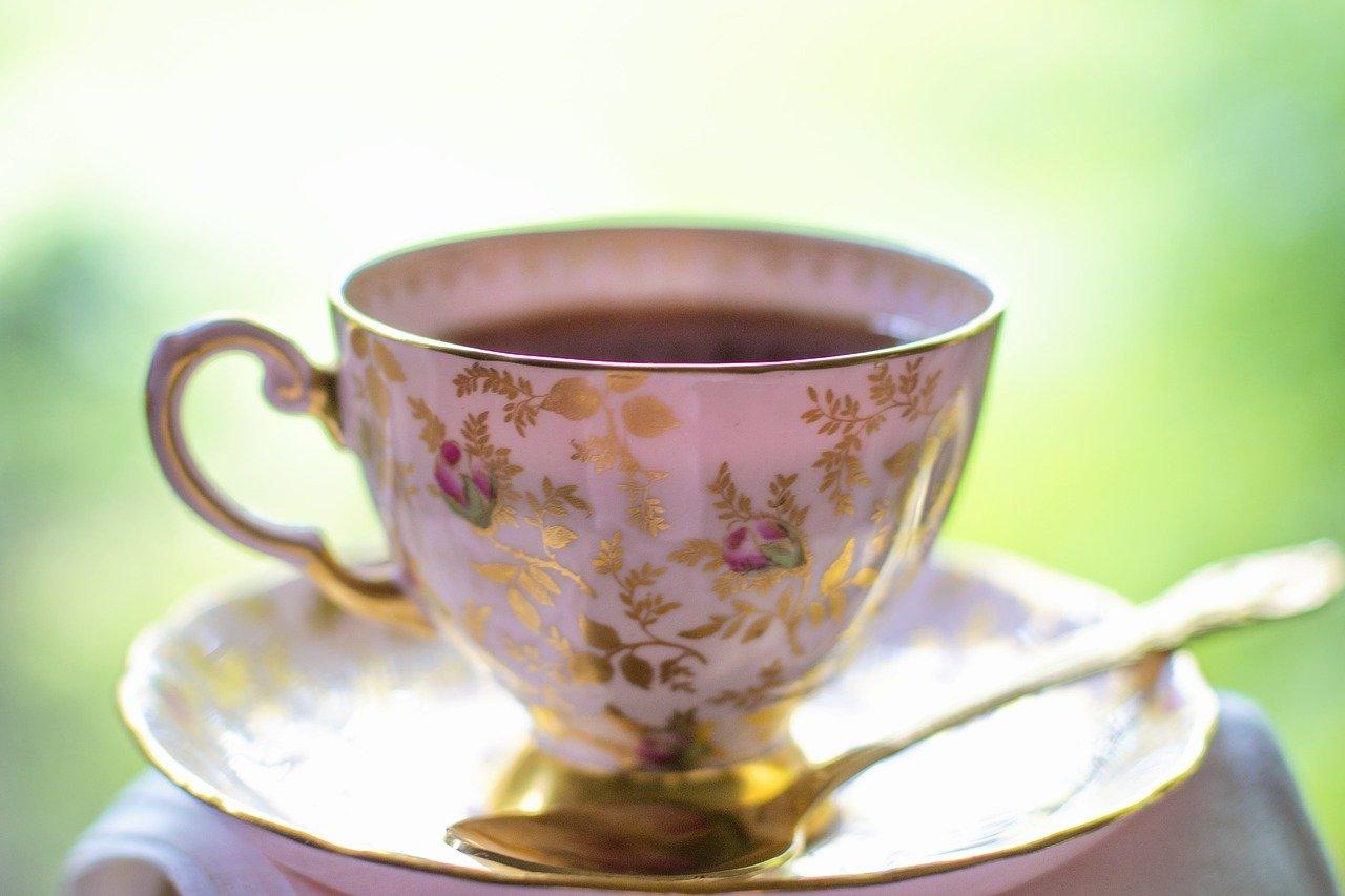 Koristeellinen kahvikuppi, jossa on kahvia ja vieressä kultalusikka.