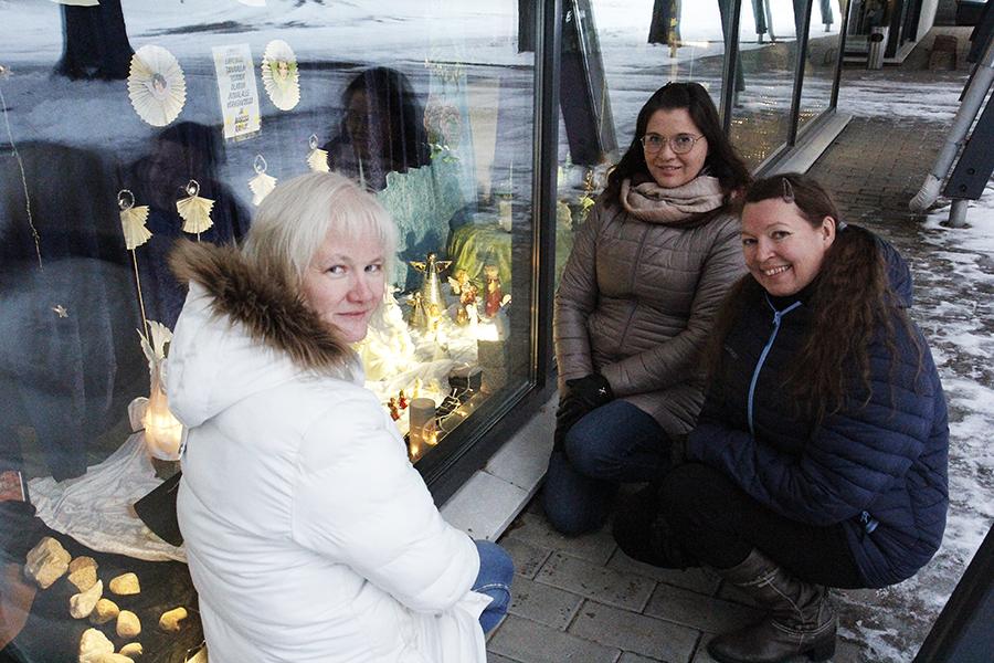 Oili Kajava, Tiina Kemola ja Kaija Luukkonen ovat kyykistyneet Kiimingin seurakuntatalossa olevan jouluikkunan eteen.