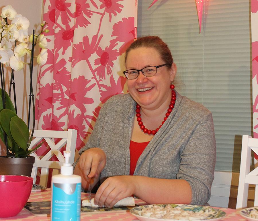 Maija Saviniemi istuu ruokapöydän takana.