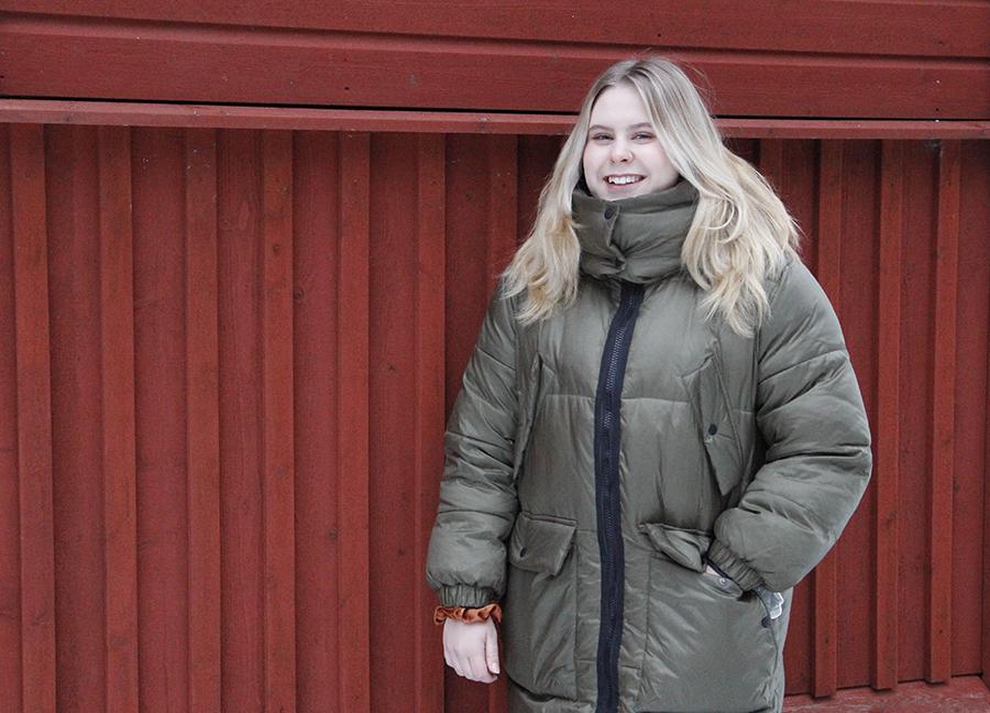 Micaela Järvenpää seisoo punaisen seinän edessä ja hymyilee.