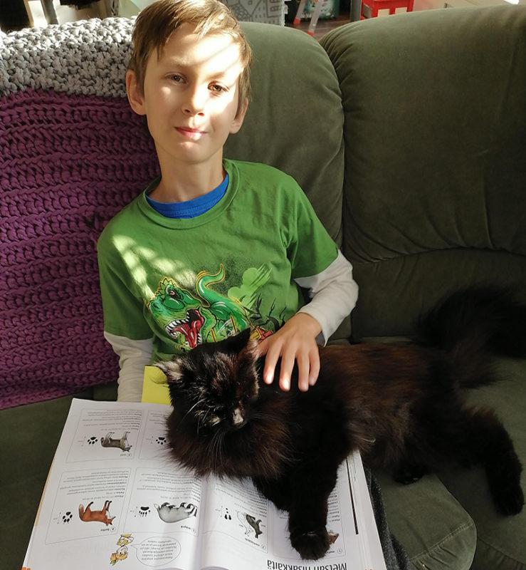Paavo Oinas istuu sohvalla sylissään kissa ja koulukirja.