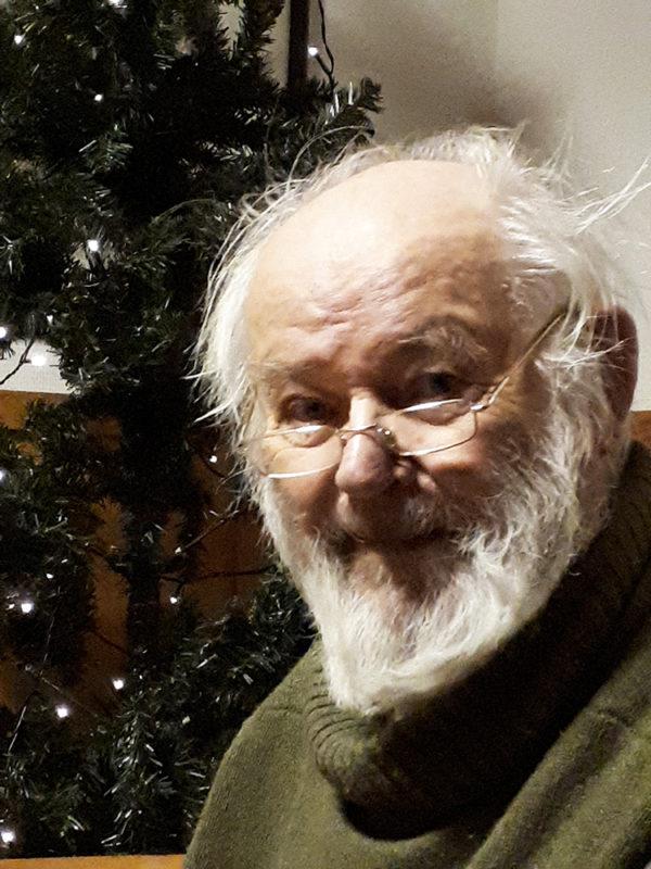 Tapio Isola katsoo kameraan ja hymyilee, taustalla on joulukuusi.