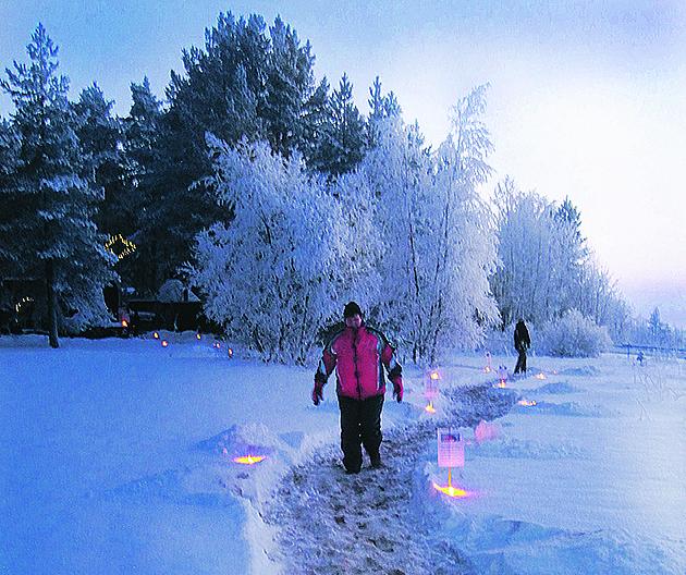Henkilö kävelee hämärtyvässä illassa pitkin lumista polkua, jonka varrella on lyhtyjä.