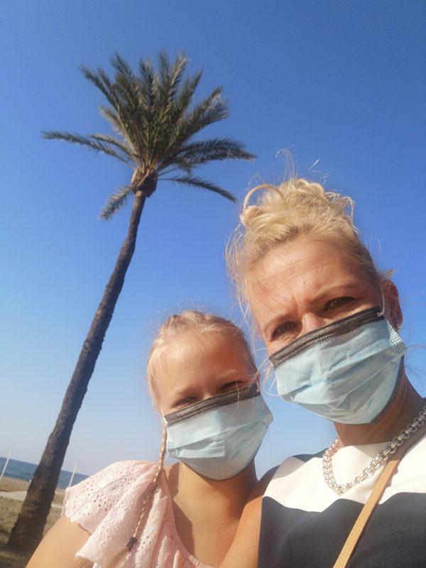Lempi ja Marja Forsblom auringonpaisteessa, maskeihin pukeutuneina palmun alla.