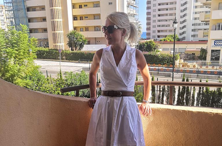 Marja Forsblom seisoo parvekkeella auringonpaisteessa.