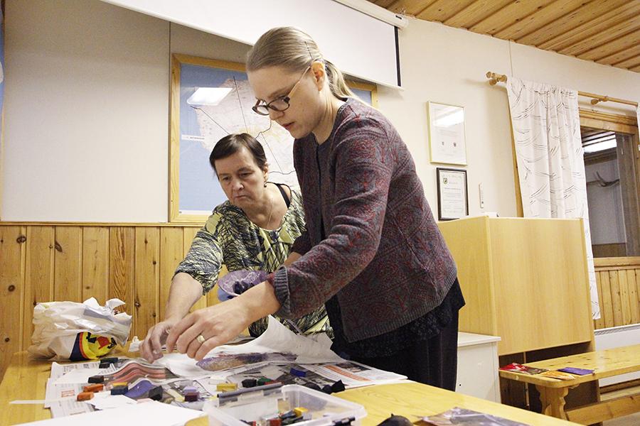 Sonja Vähämetsä sulattaa mehiläisvahaa kortin päälle Ulla Sauvolan opastuksella.