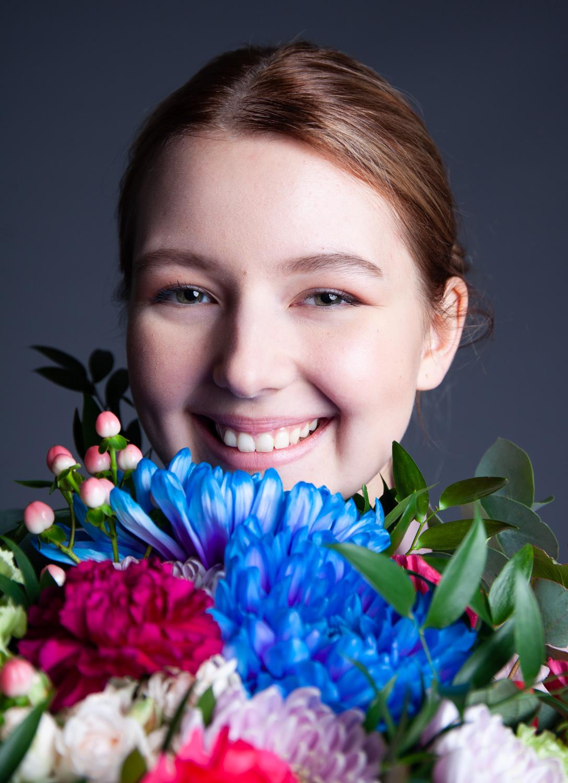 Nuori nainen pitää kasvojensa edessä kukkakimppua ja hymyilee.