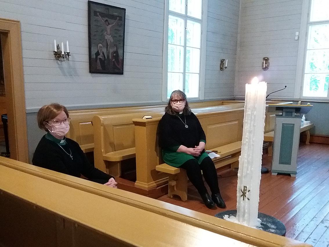 Kaksi seurakunnan diakoniatyöntekijää istuu kirkossa edessään iso palava kynttilä.