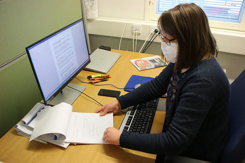 Nainen selaa työpöydän ja tietokoneruudun ääressä muistiinpanojaan.
