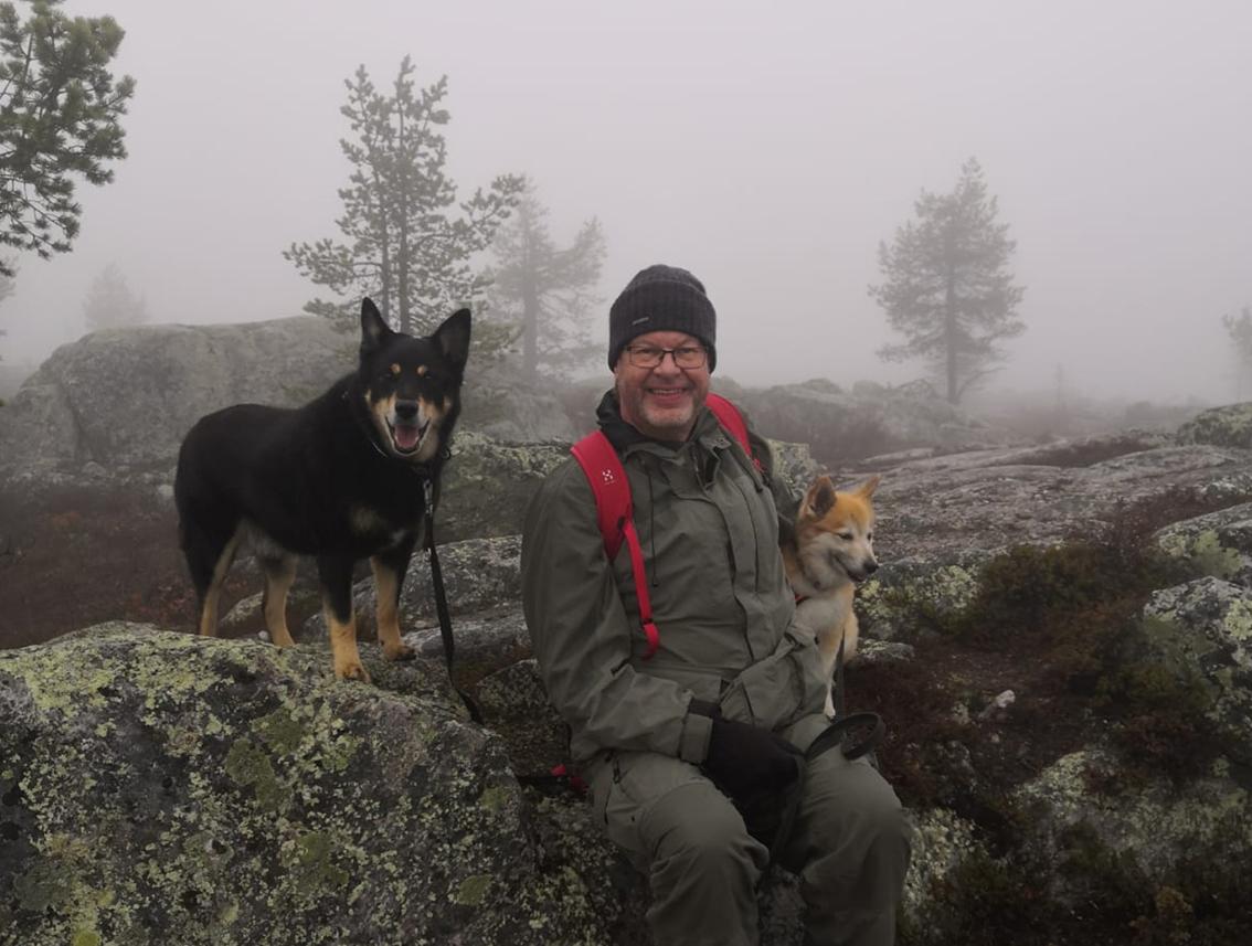 Vaellusvarusteisiin pukeutunut mies istuu kalliolla kaksi koiraa seuranaan.