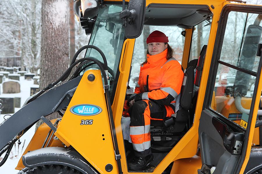 Hautausmaalla työskentelevä Juha Mikkonen istuu traktorin kopissa ja katsoo kameraan.