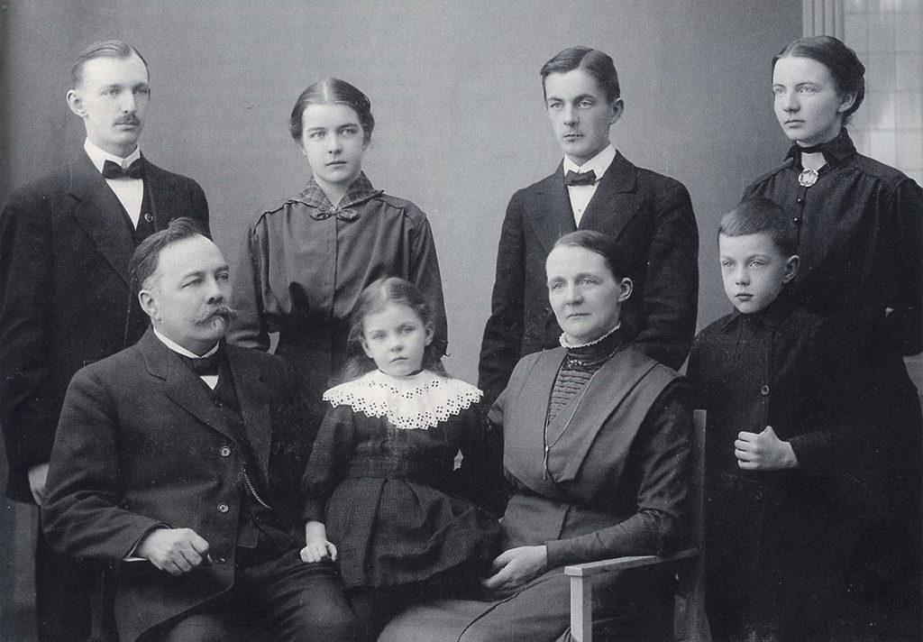 Mustavalkoisessa perhepotretissa isä ja äiti istumassa kuusi eri-ikäistä lasta ympärillään.
