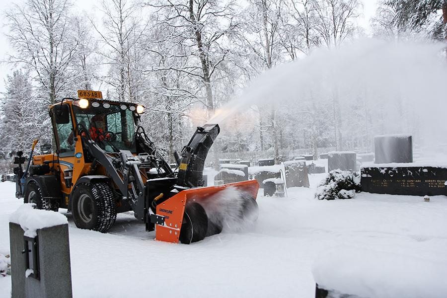 Traktori linkoaa lunta Intiön hautausmaalla.