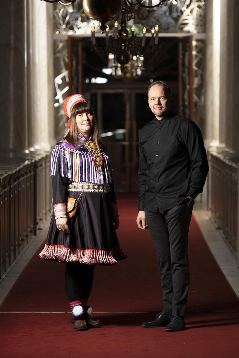 Anna Näkkäläjärvi-Länsman ja Raimo Paaso seisovat kirkon käytävällä vierekkäin.