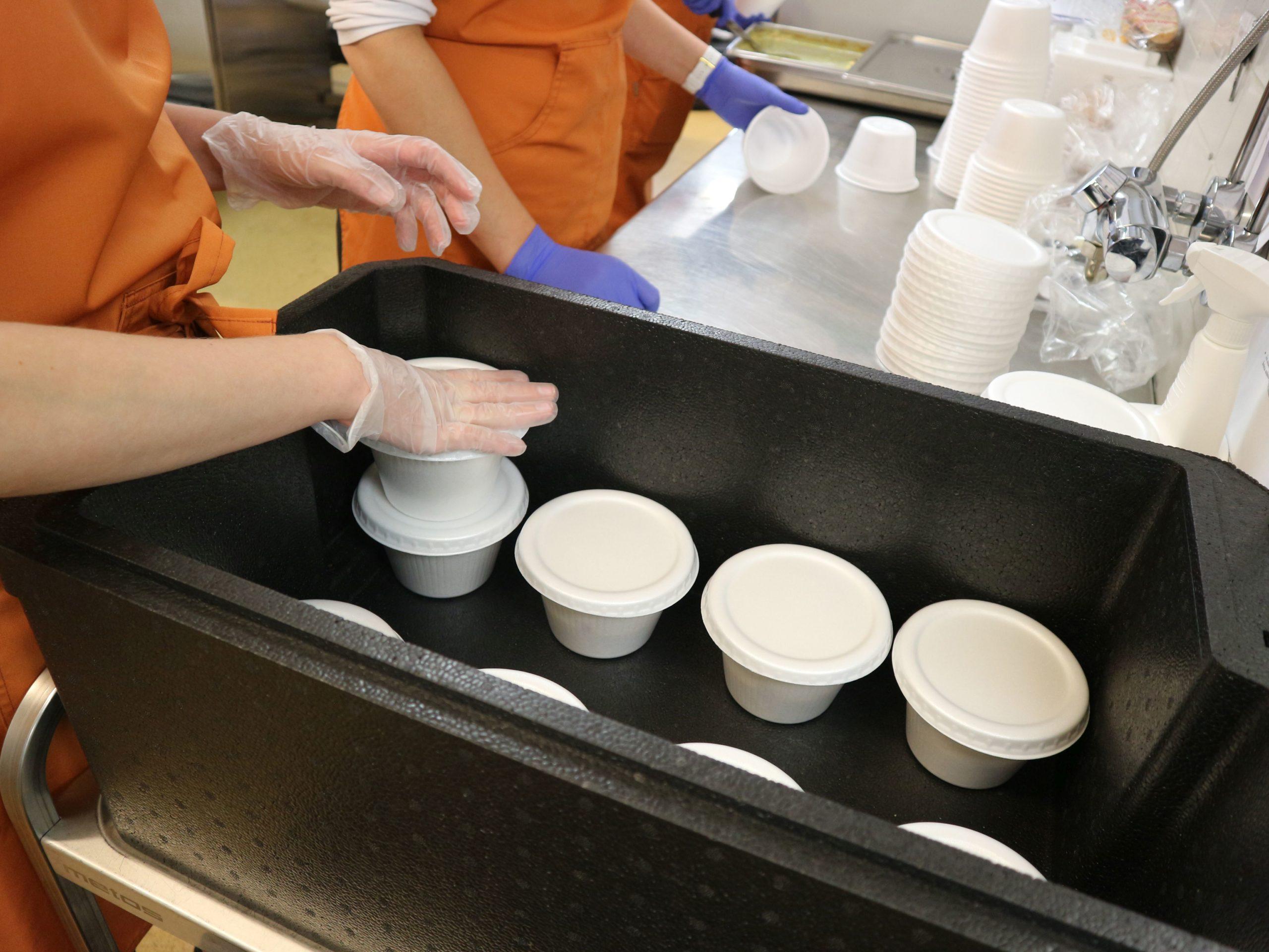 Lämpölaatikkoon pakataan valkoisia ruokarasioita. Kuvassa näkyy myös kaksi käsiparia muovihanskat käsissään.