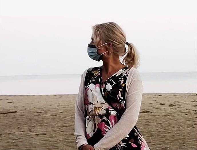 Kesämekkoon pukeutunut nainen katsoo kaukaisuuteen merenrannalla.
