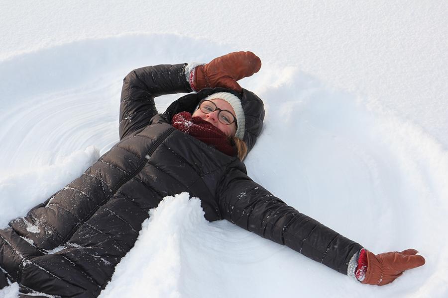 Ulla Rissanen makaa lumessa ja tekee lumienkeliä.