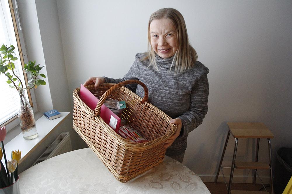 Mari Jääskeläinen pitää käsissään koria, jossa on tarvikkeita pyhäkoulua varten.