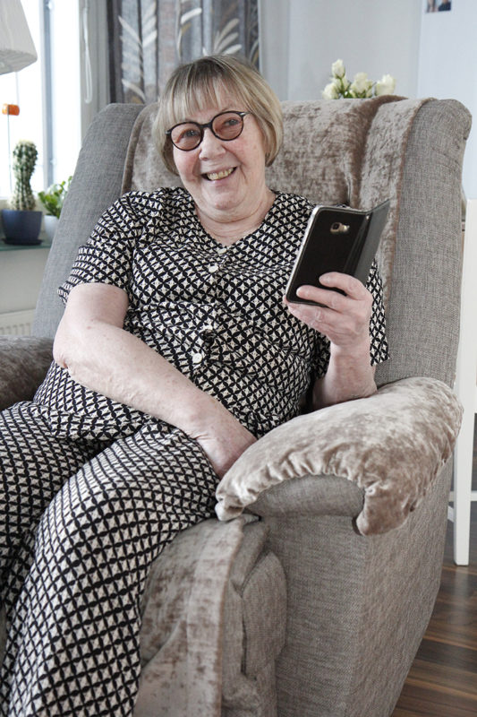 Ritva Ruottinen istuu nojatuolissa kädessään puhelin.