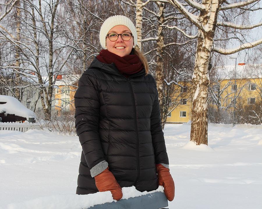 Ulla Rissanen seisoo ulkona ja hymyilee.