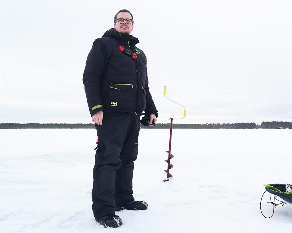 Juha Penttinen seisoo jäällä pilkkihaalarissa, taustalla jääkaira.
