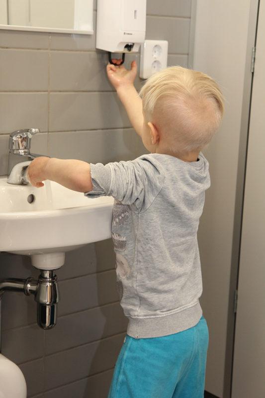 Poika pesee käsiään lavuaarin ääressä ja ottaa saippuaa automaatista.