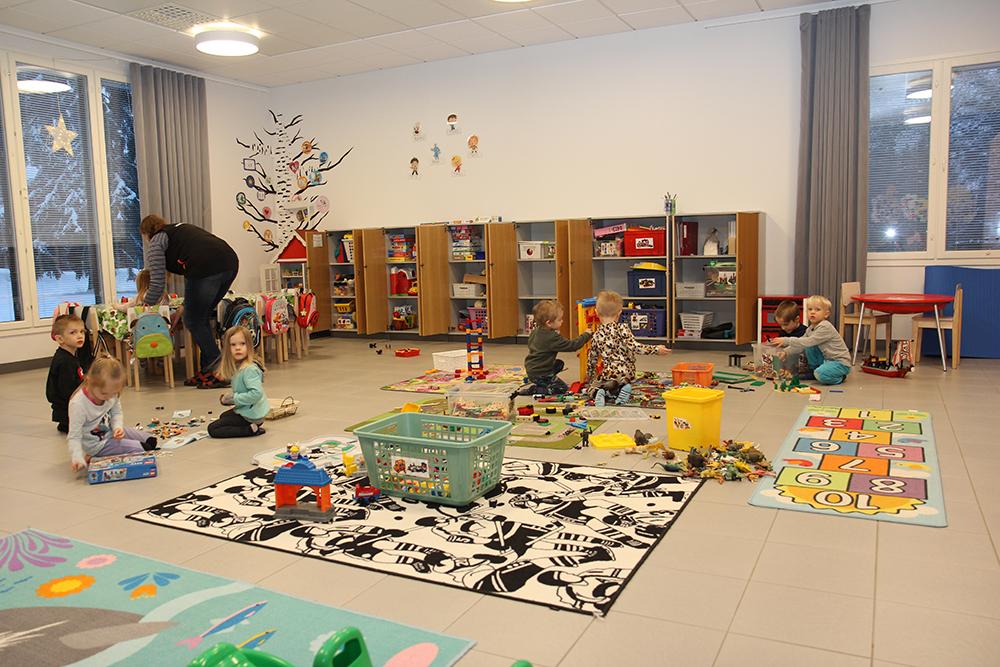 Joukko lapsia leikkii isossa huoneessa, jossa on paljon leluja.